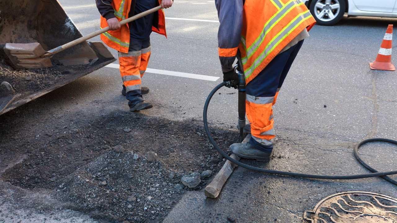 Road maintenance removes old asphalt with jackhammer