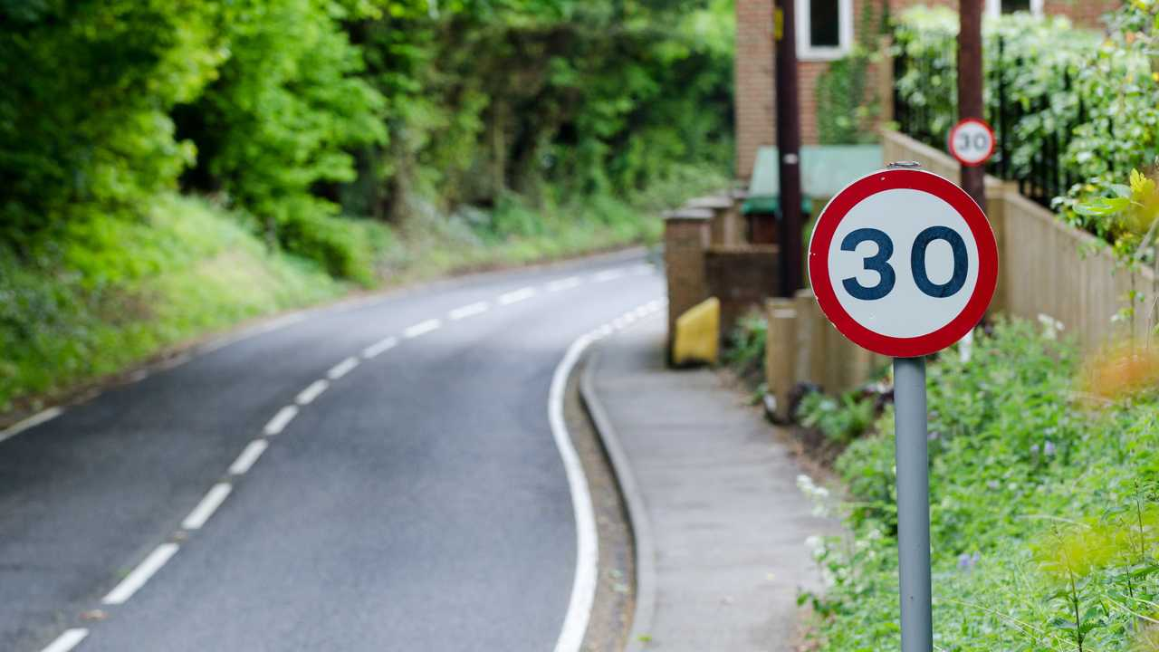 30 mph speed limit sign on side of road in UK