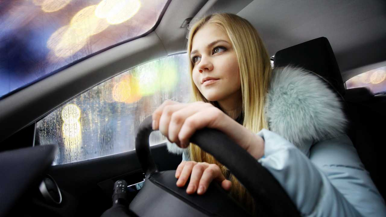 Young woman driving in the rain