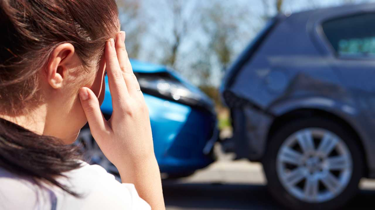 Stressed woman driver sitting at roadside after traffic accident