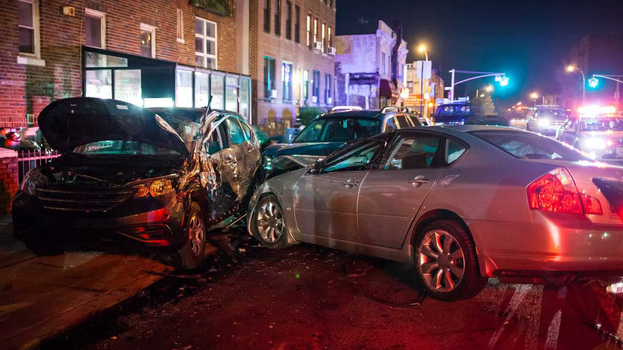 Multiple car crash with heavy damage in city at night