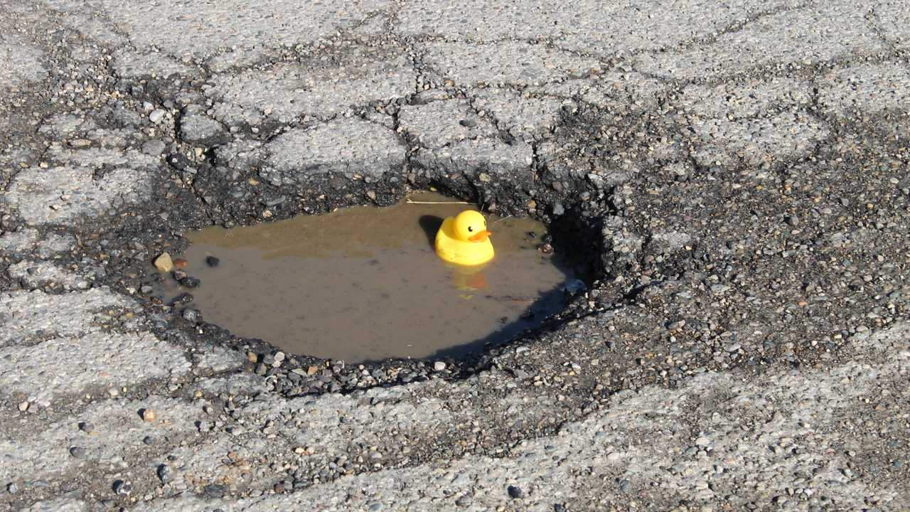 Large pothole filled with water with rubber ducky