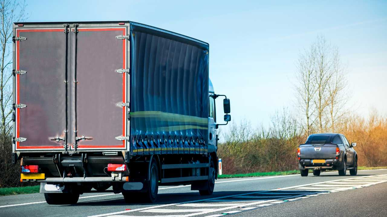 Big lorry truck and normal pickup truck on motorway