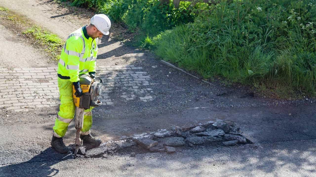 Road worker repairing pothole in Buckingham UK