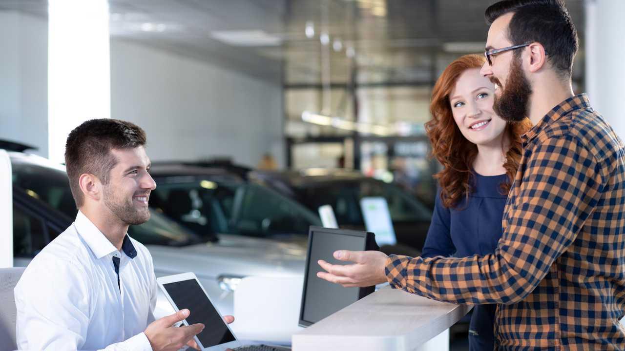 Car buyers talking with salesman in showroom