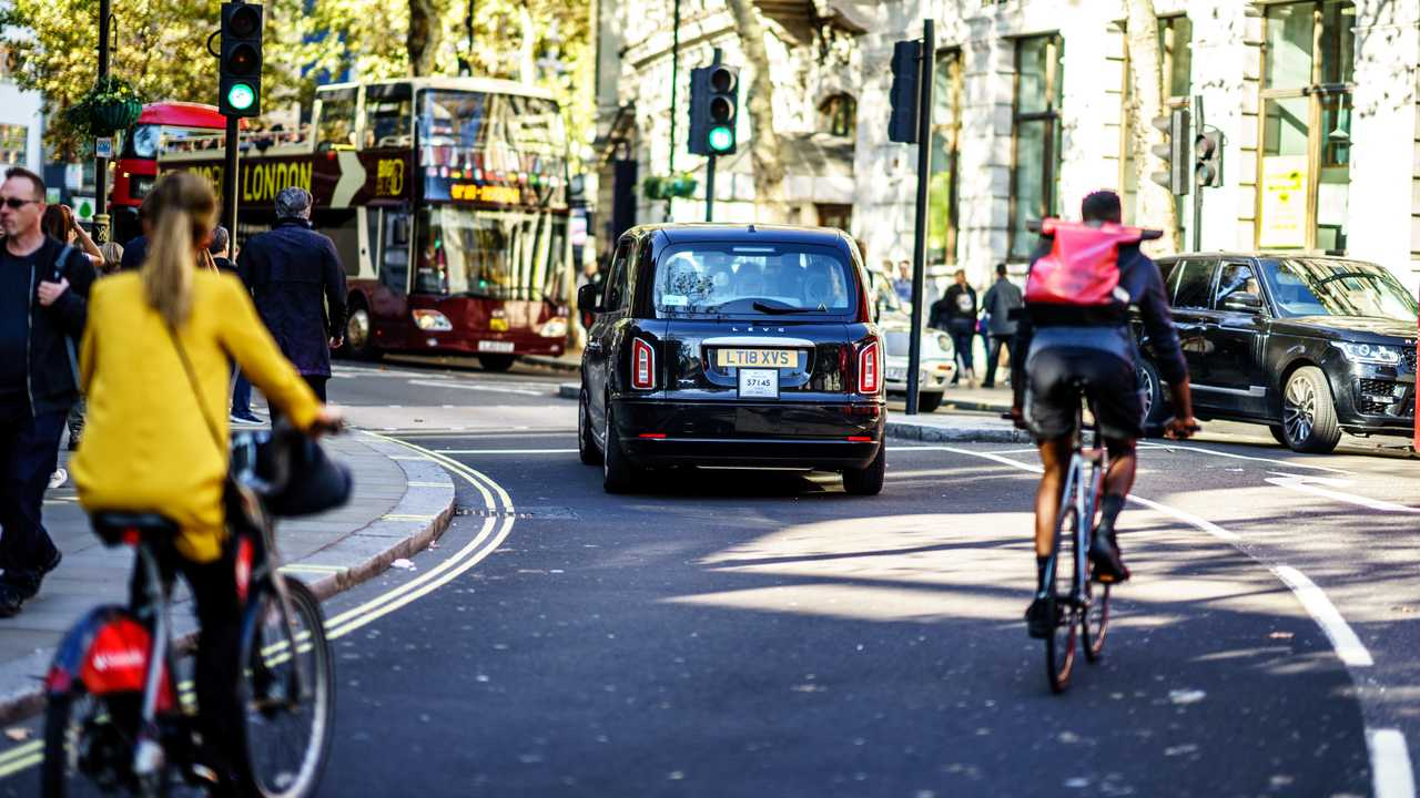 Electric taxi cab and cyclists with other traffic on the street in London