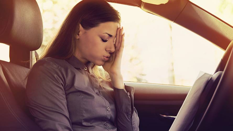 Stressed woman driver with papers sitting inside her car