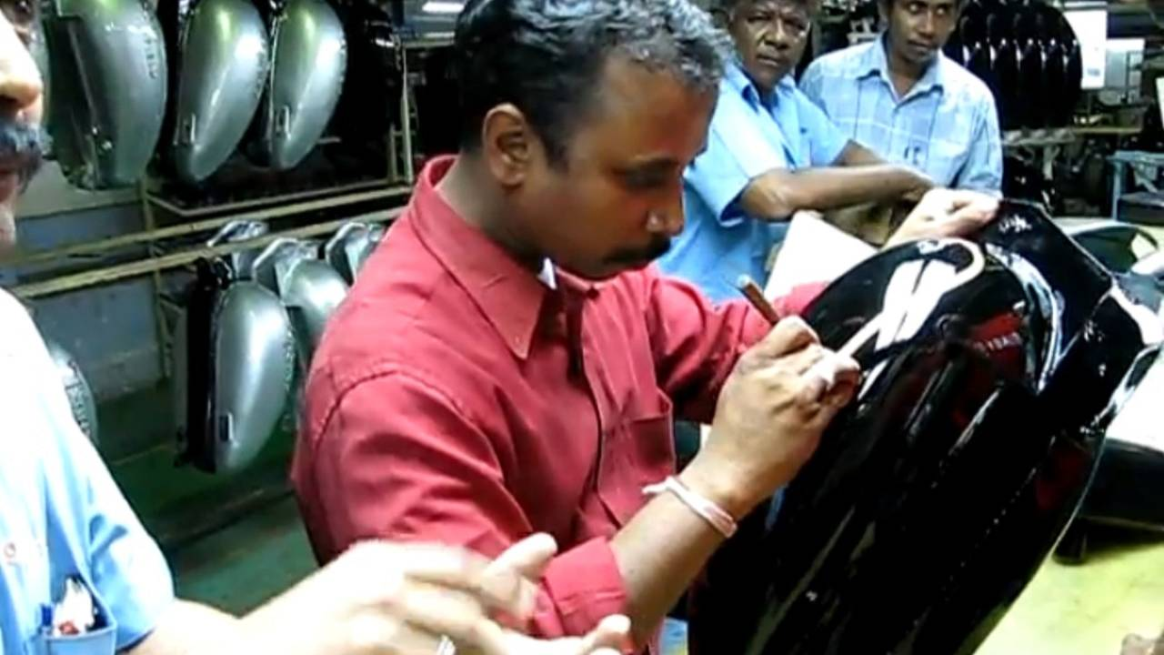 Hand painting a Royal Enfield fuel tank