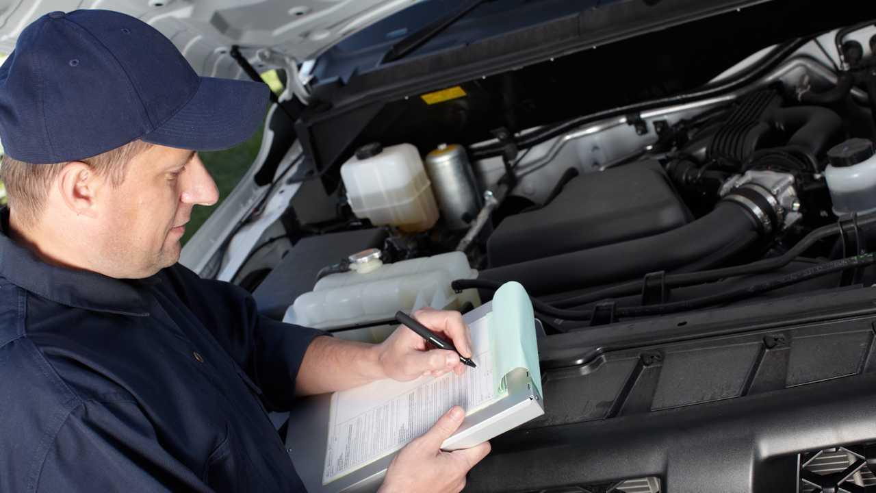 Mechanic inspecting car in service garage