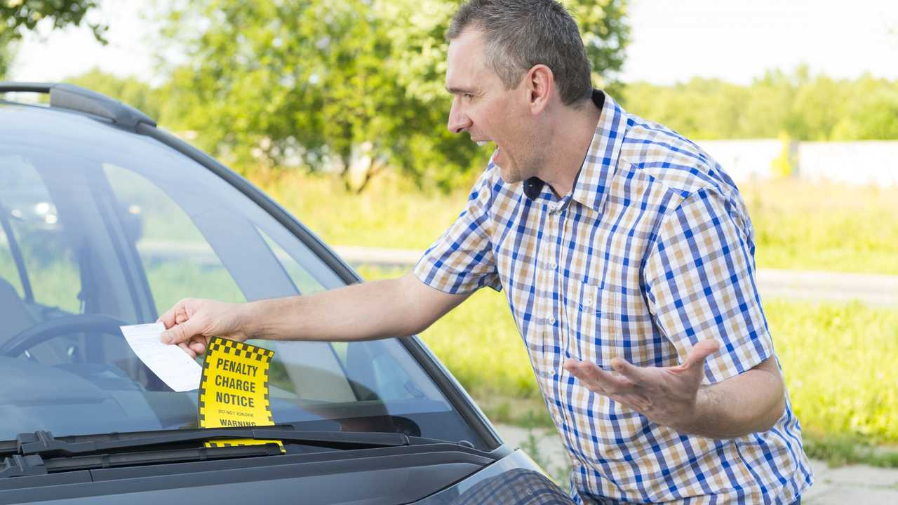 Suprised man discovers parking ticket under windscreen wiper