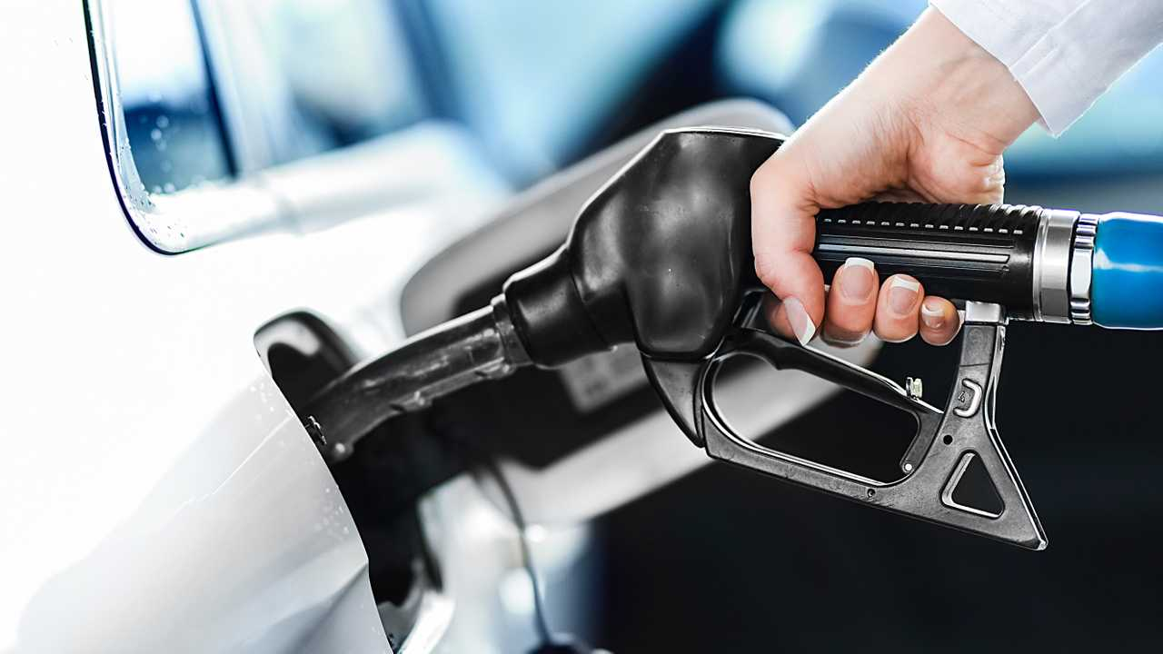 Woman pumping petrol at fuel station into car