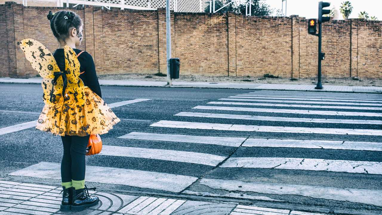 Little girl waiting at zebra crossing in halloween costume