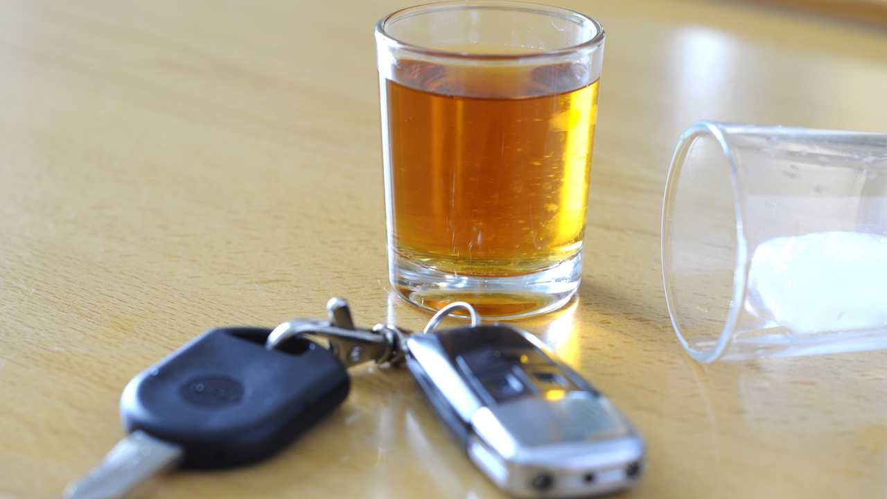 Alcoholic drink and car keys on table