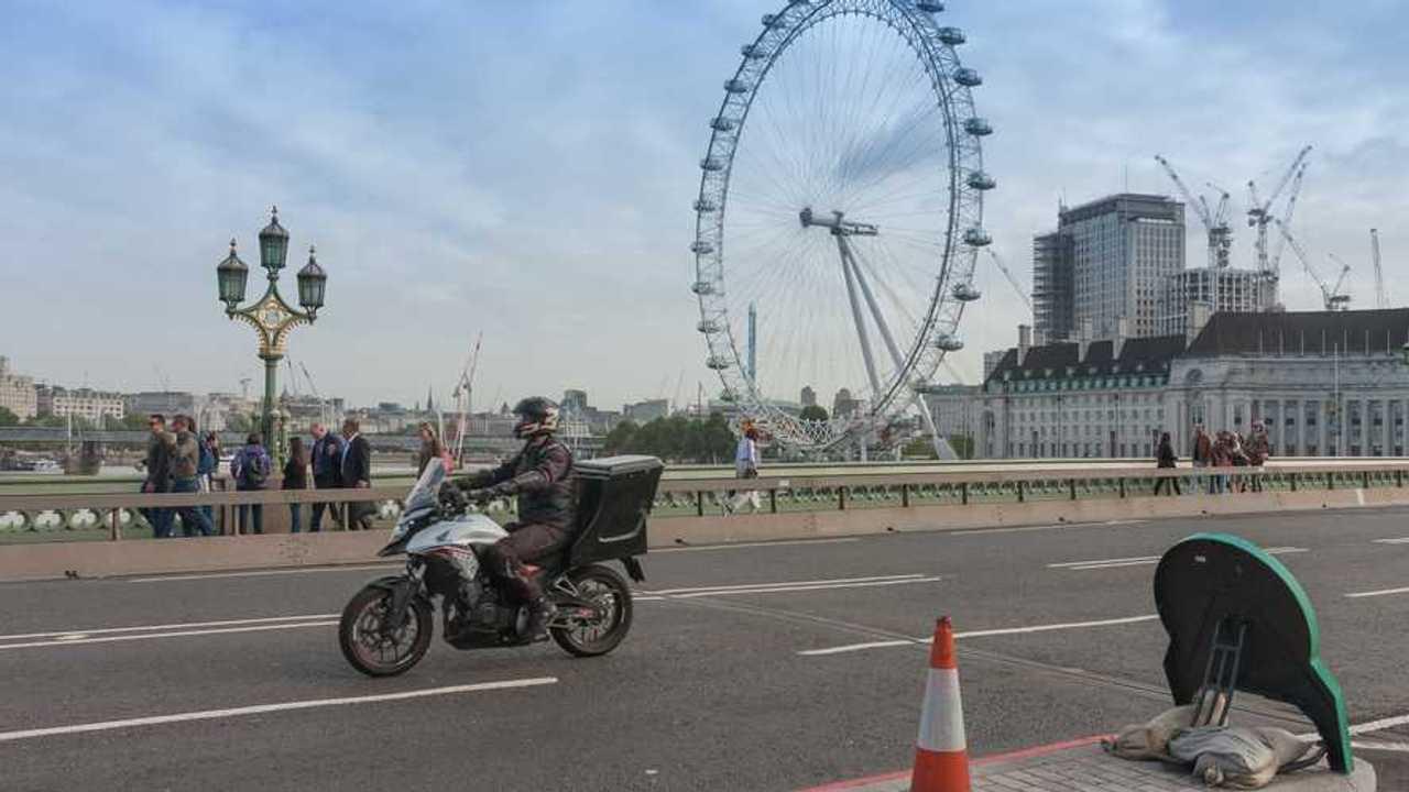 Tourists walking and traffic on Westminster Bidge man on Honda bike