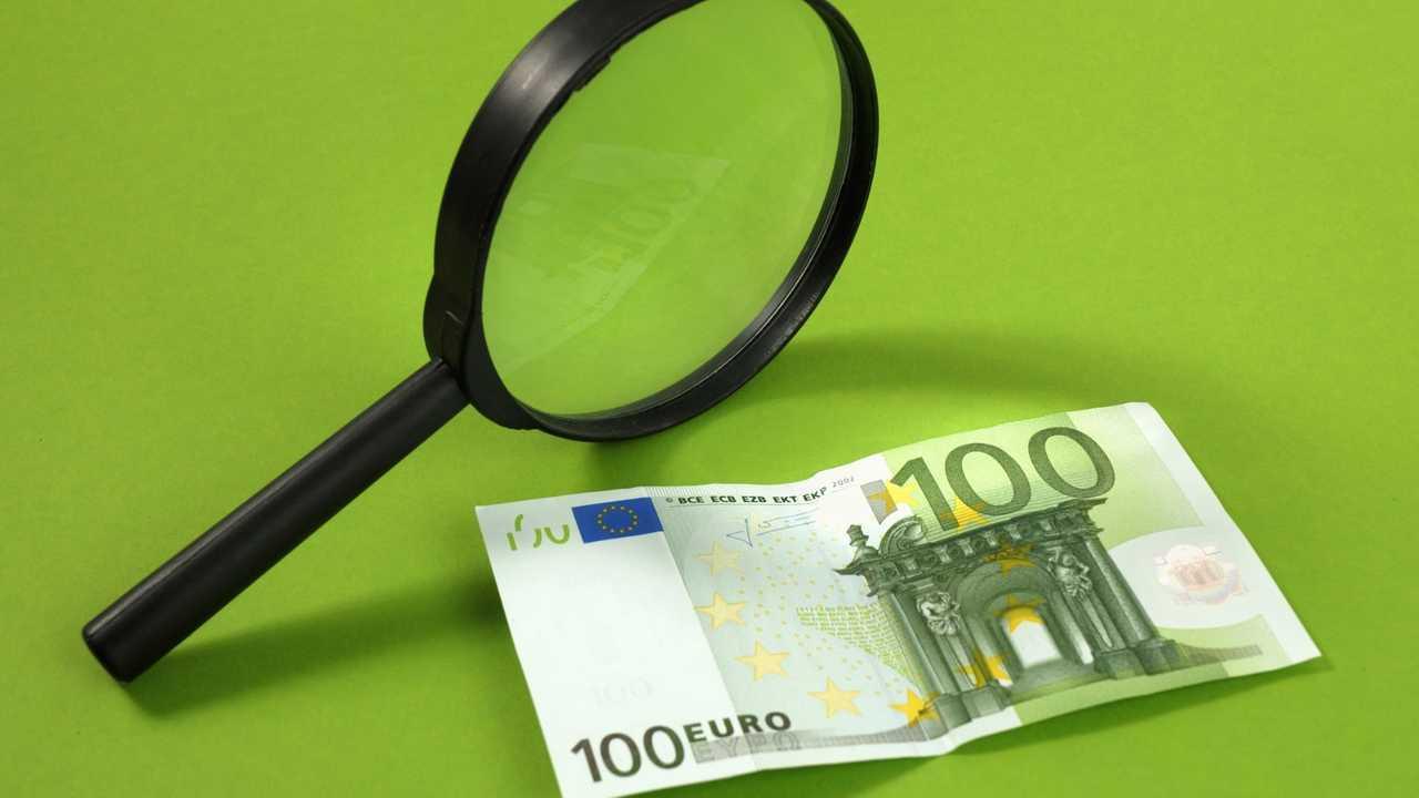Una lente di ingrandimento e una banconota da 100 euro