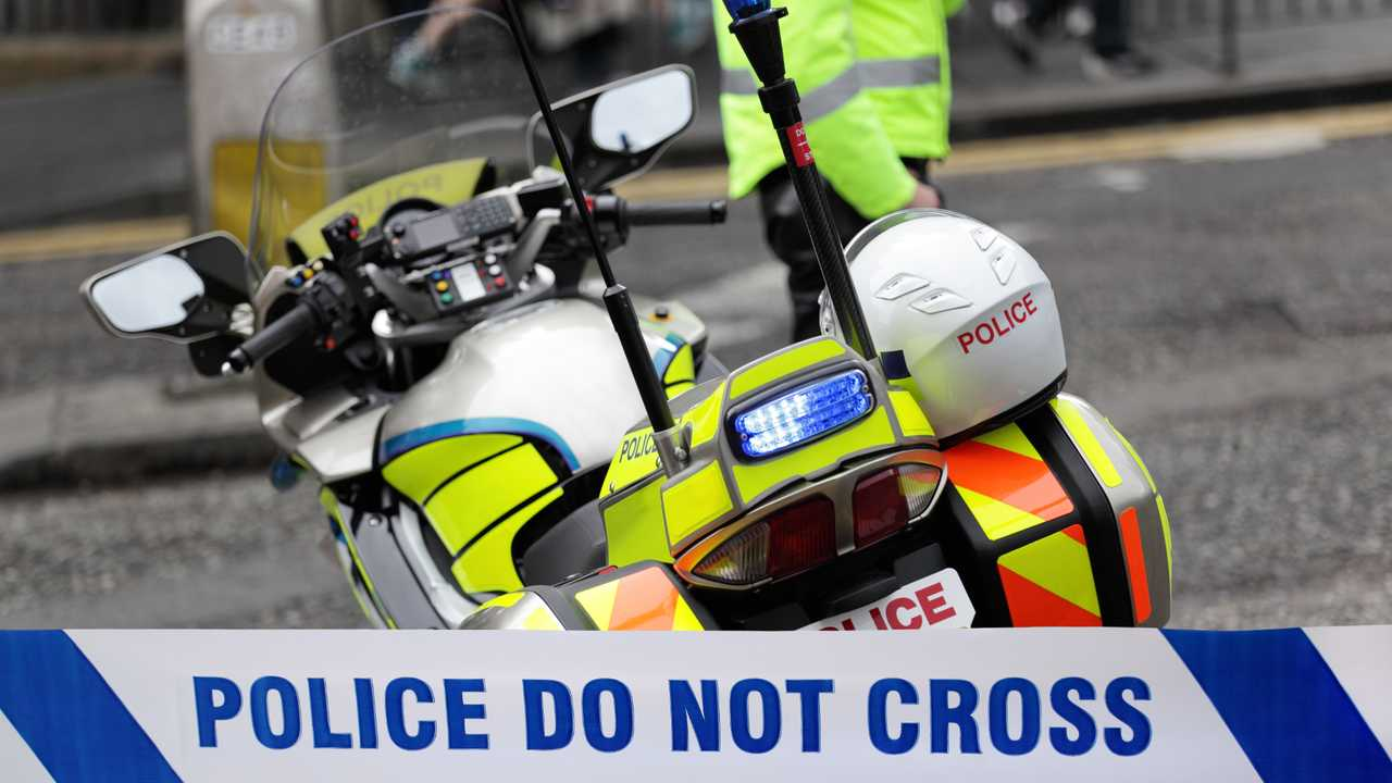 Policeman and motorcycle behind cordon tape at an accident