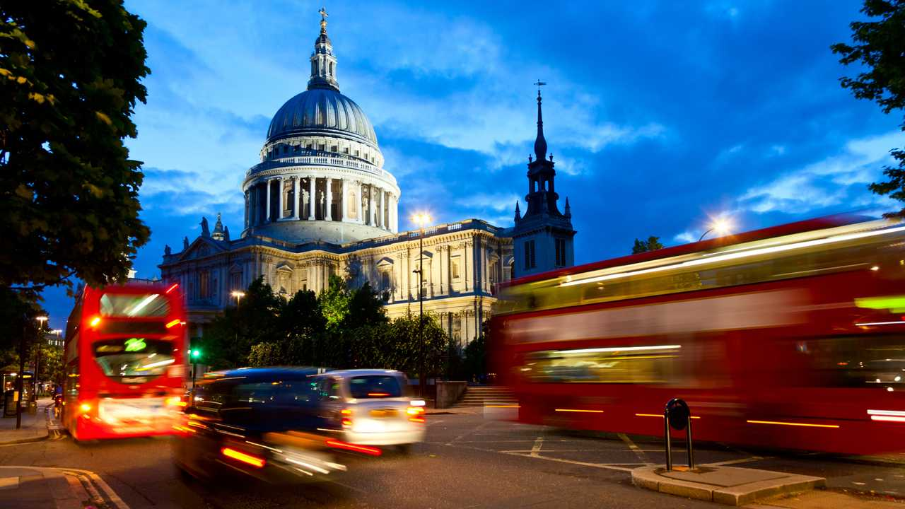 Buses passing Saint Paul's Cathedral London in evening