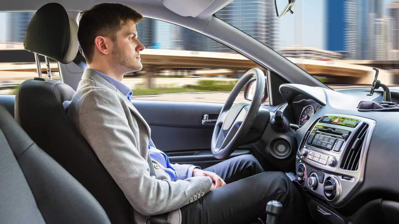 Man sitting inside autonomous car without hands on steering wheel