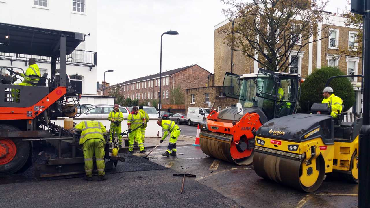 Workers lay asphalt on a road with paver machine in London UK