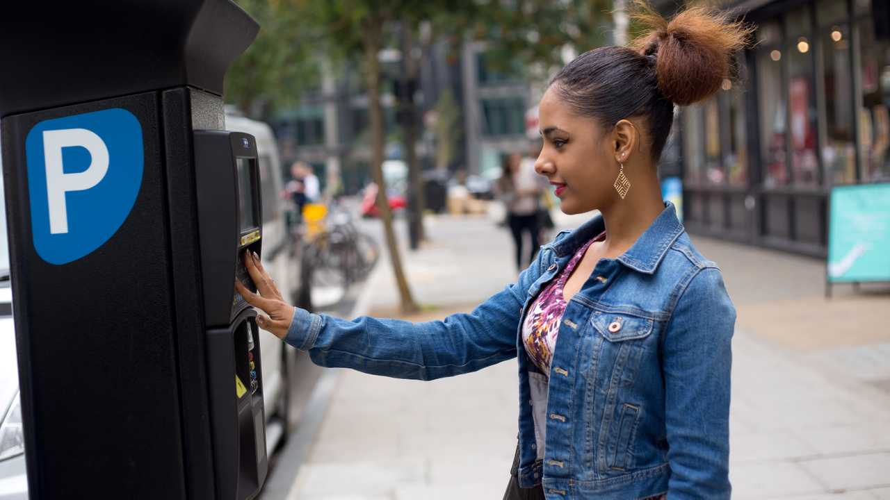 Woman using pay and display parking ticket machine