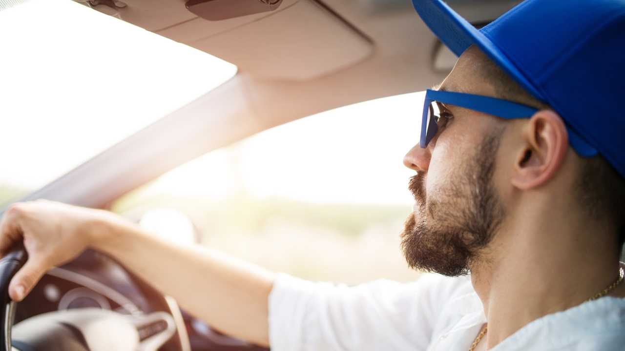 Young man driving car in sunshine