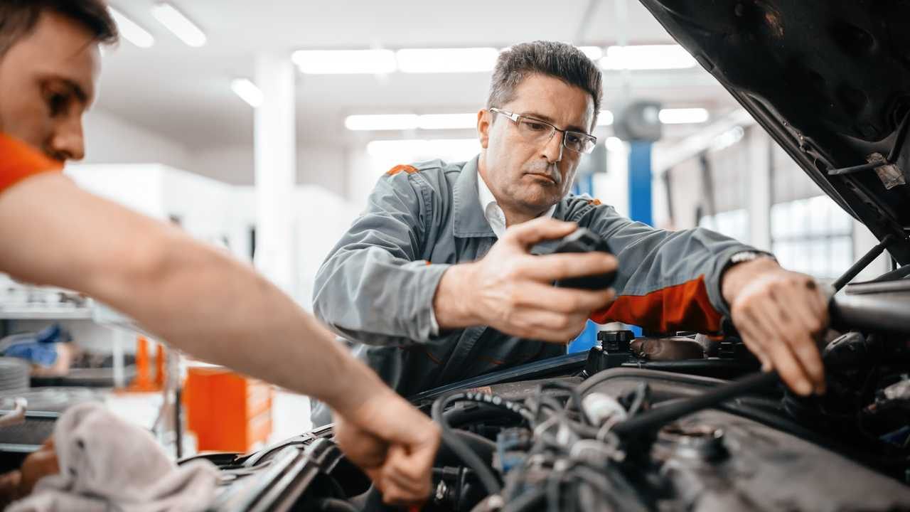 Car mechanics working in engine area