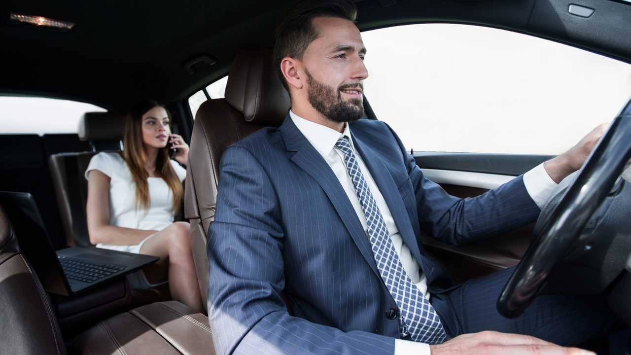 Upscale private hire taxi driver with woman passenger