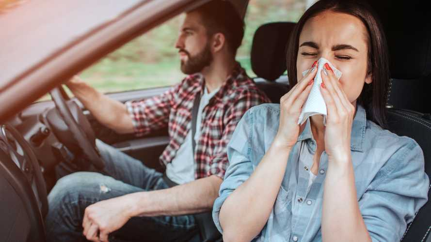 Woman passenger is sneezing into tissue paper
