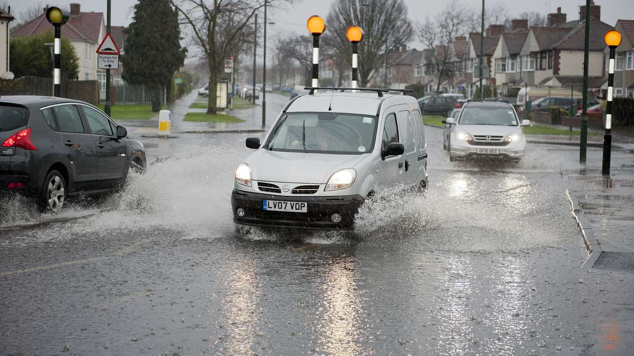 Cars drive through flooded road in Sidcup UK