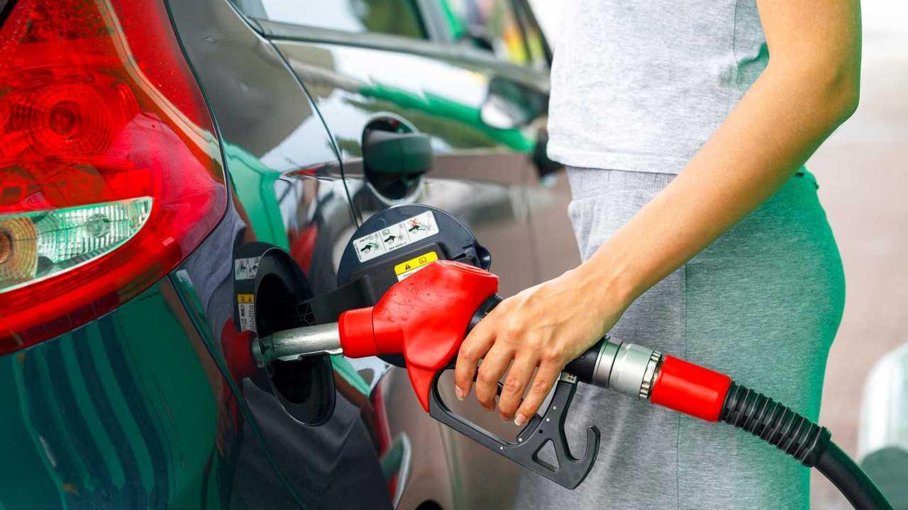 Woman fills car at petrol station