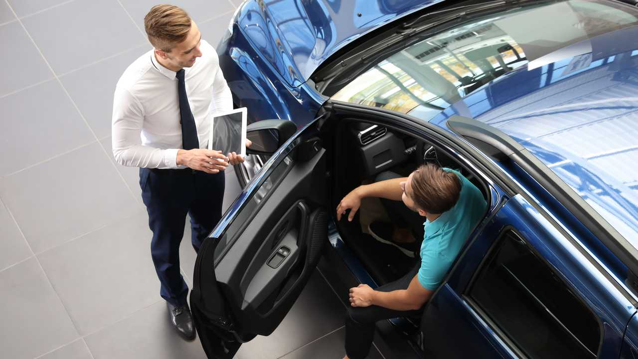 Car salesman working with client in dealership