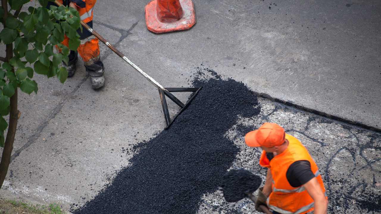 Workers resurfacing street with fresh asphalt
