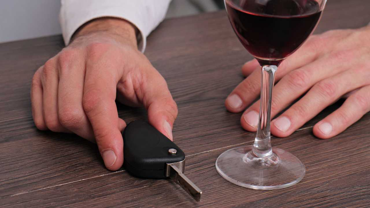 Man drinking wine and holding car keys