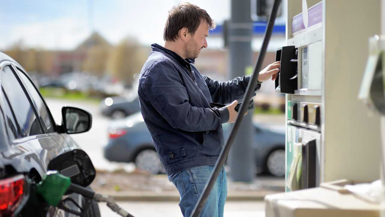 Man making fuel pump payment at petrol station