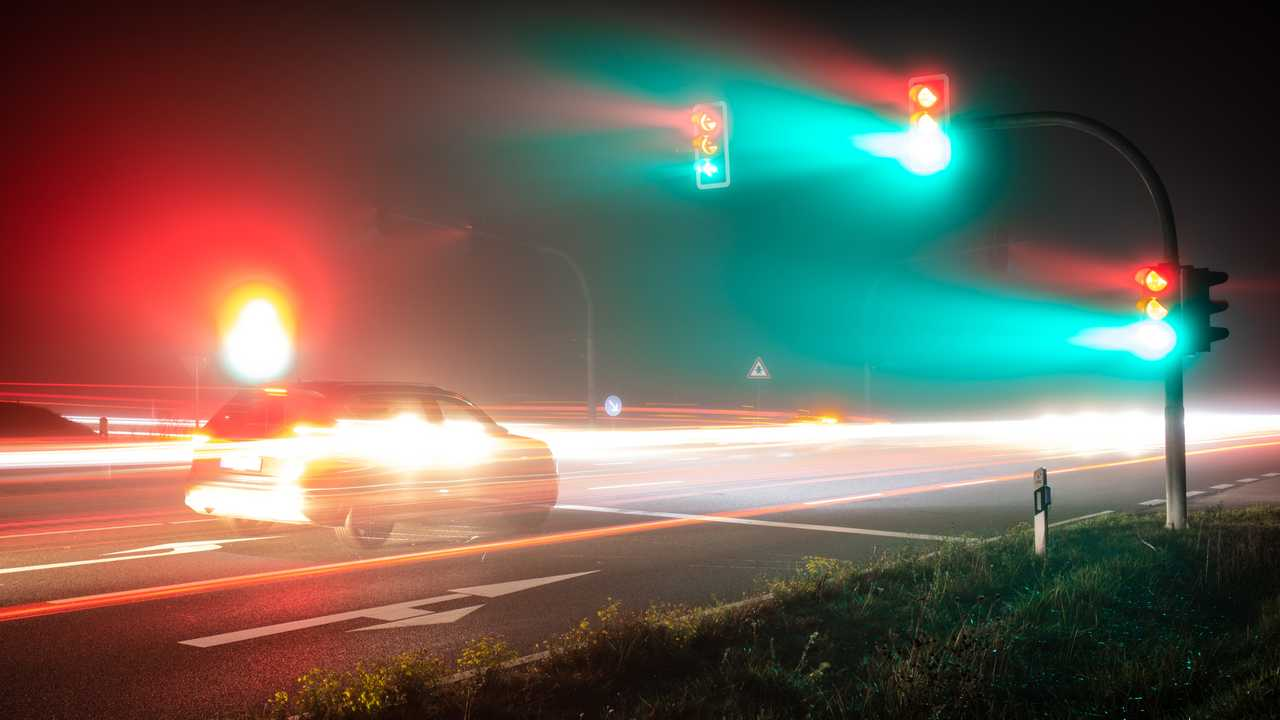 A car speeds through a red traffic light.