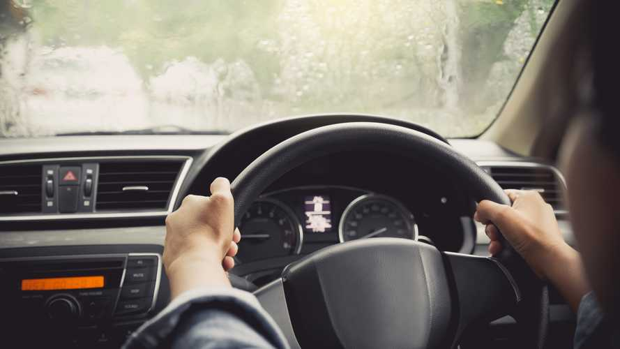 Driver gripping steering wheel tightly while driving in rain