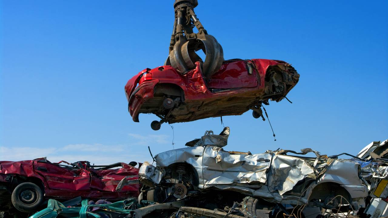 Crane picking up car in junkyard