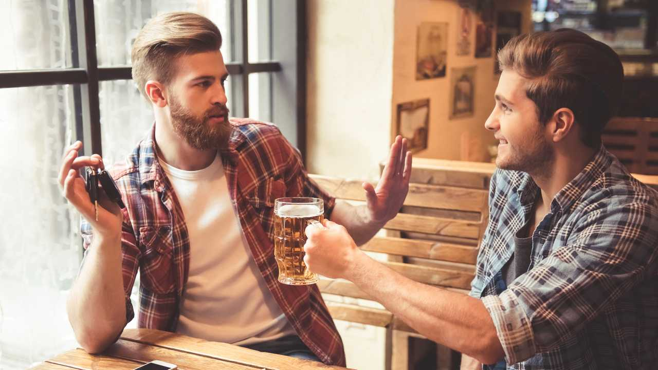 Man holding car keys refuses beer drink