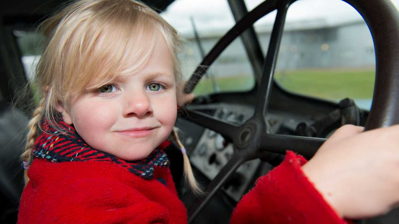 Cute little girl holding steering wheel of a vintage lorry