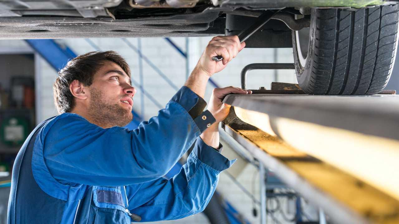 Mechanic examining suspension of vehicle
