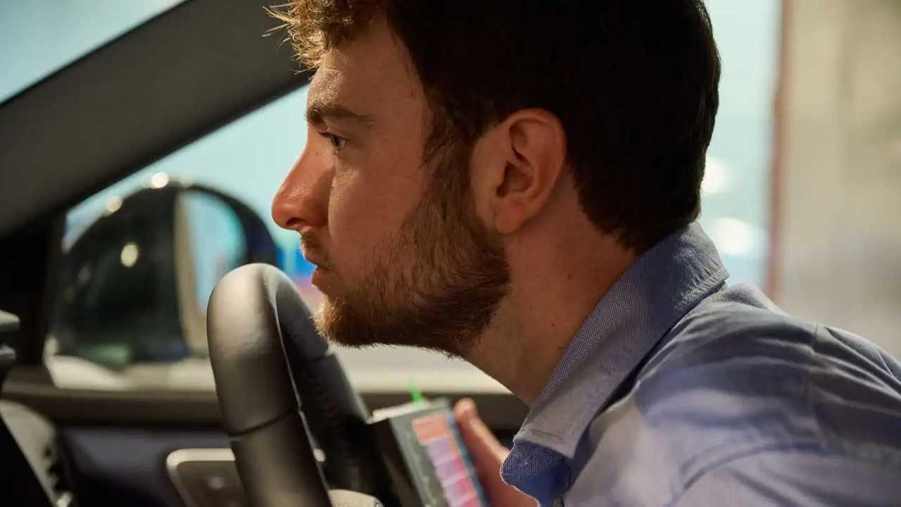 un uomo annusa il volante di un'auto