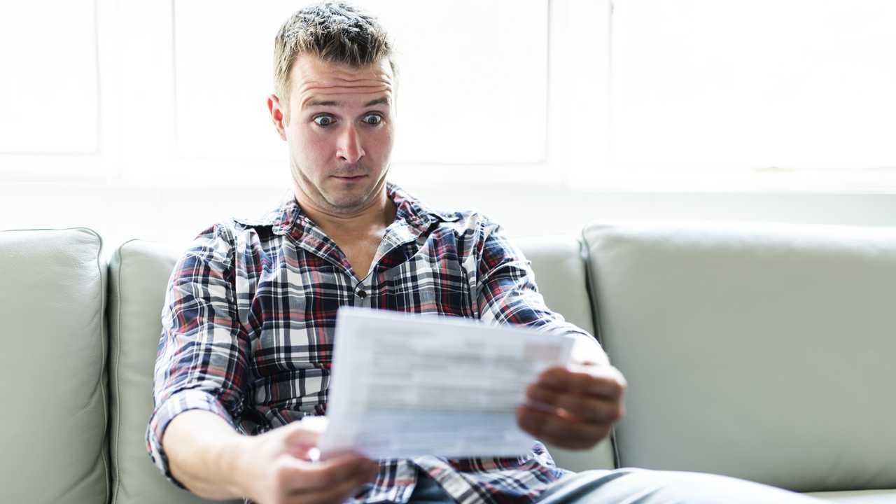 Shocked man holding some documents on sofa