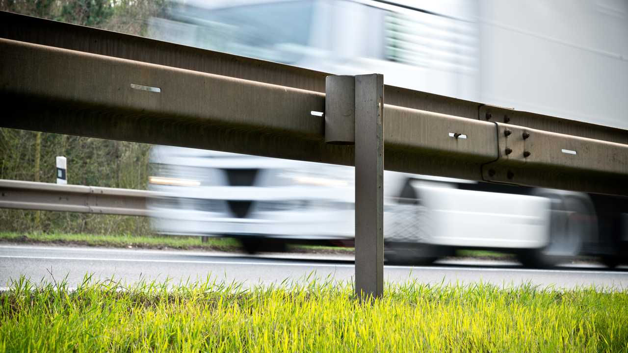 Roadside crash barrier with passing lorry