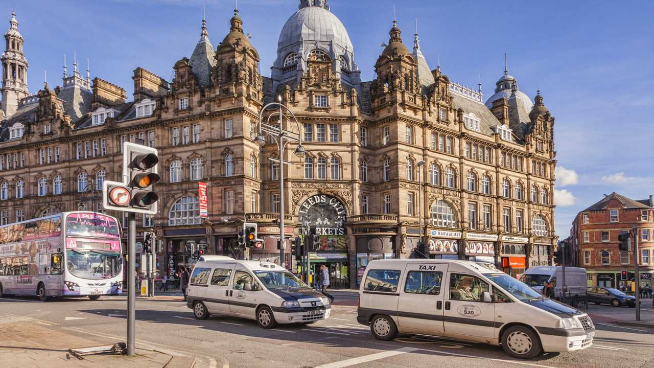 Taxis and a bus passing the Leeds City Markets West Yorkshire UK