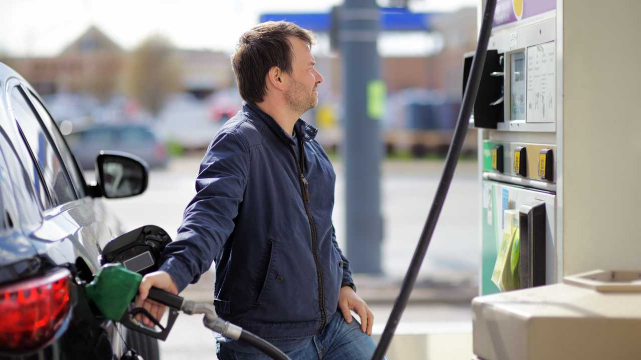 Man filling fuel in car holding nozzle