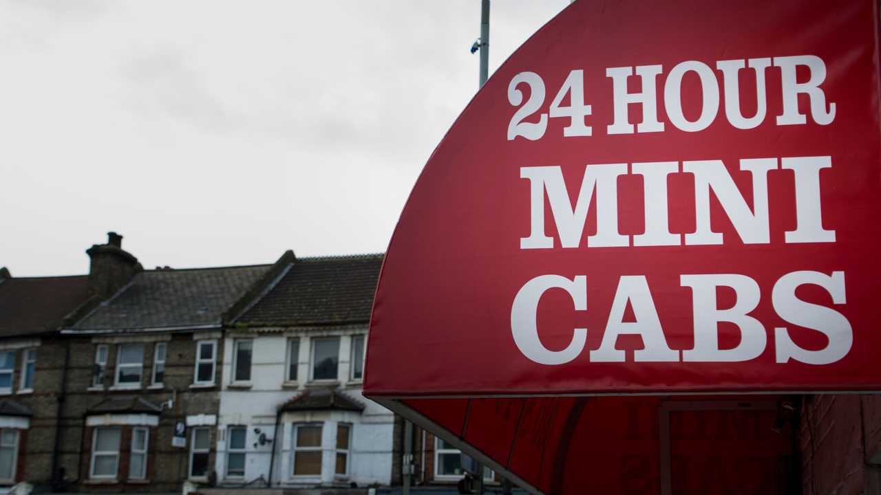 UK high street 24 hour mini cabs sign