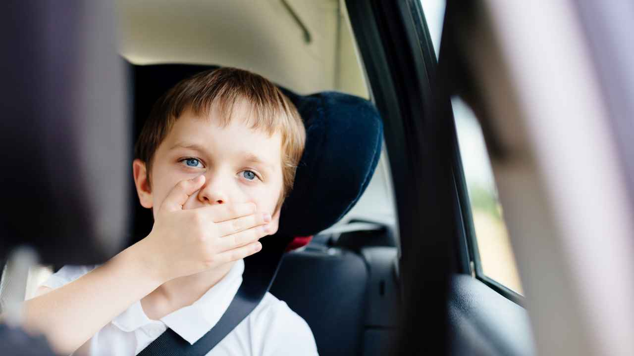 Child in backseat of car covers his mouth with his hand