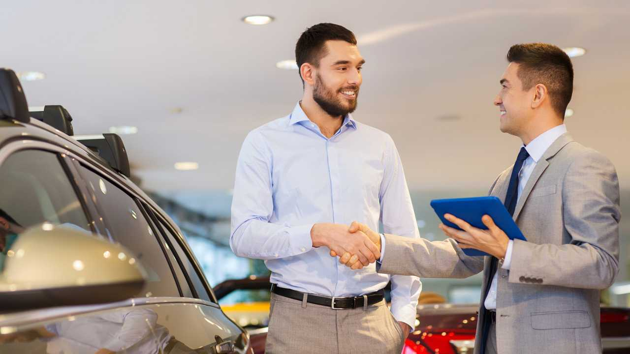 Man and car salesman shaking hands in auto show room