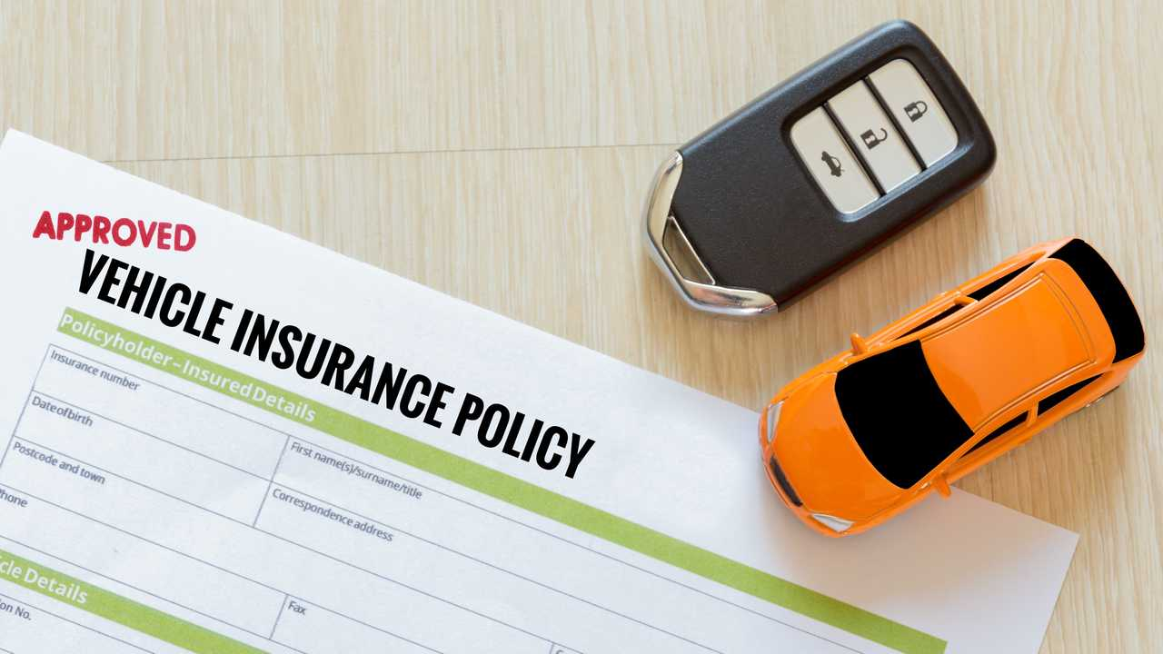 Top view of approved vehicle insurance policy with car key and car toy on wooden desk