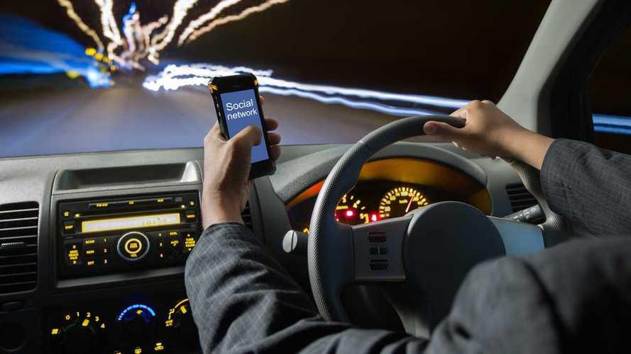 Man using smart phones while driving at night